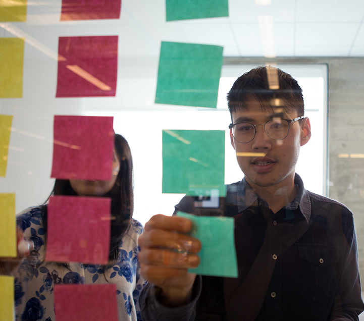 Man with glasses adjusting post-it notes on a window