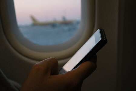 Hand with smartphone on plane.