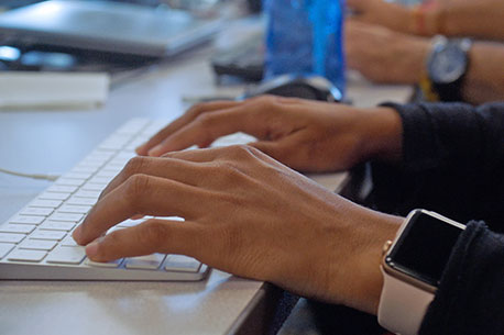 Person typing on Apple keyboard.