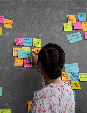 Woman sticking Post-It notes on a wall